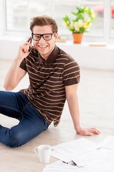Surfen im internet zu hause. blick von oben auf einen gutaussehenden jungen mann mit brille, der am laptop arbeitet, während er in seiner wohnung auf dem boden sitzt
