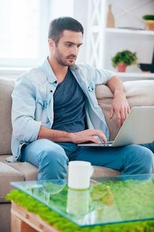 Surfen im internet zu hause. hübscher junger mann, der am laptop arbeitet, während er zu hause auf der couch sitzt