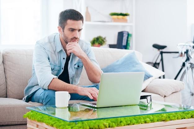 Surfen im netz zu hause. hübscher junger mann, der am laptop arbeitet, während er zu hause auf der couch sitzt
