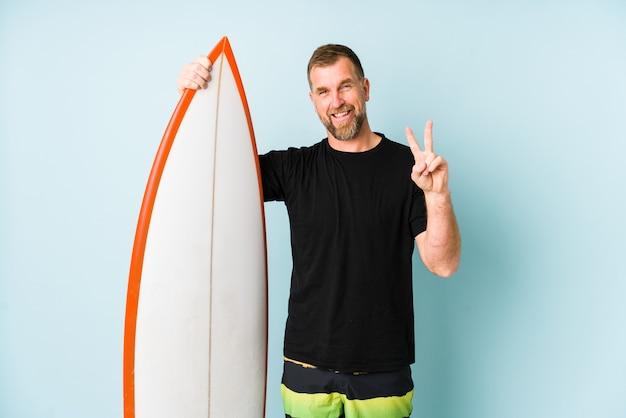 Surfen mann isoliert auf blauer wand zeigt nummer zwei mit den fingern.