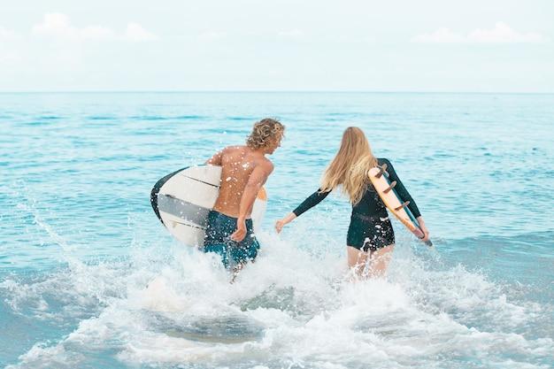 Surfer am strand - lächelnde surfer, die am strand spazieren gehen und im sommer spaß haben Premium Fotos