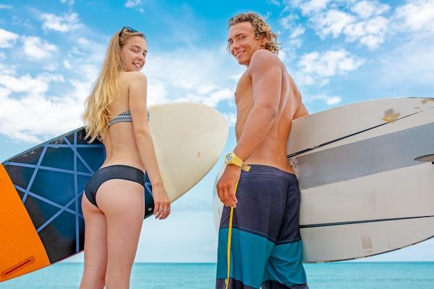 Surfer am strand - lächelnde surfer, die am strand spazieren gehen und im sommer spaß haben