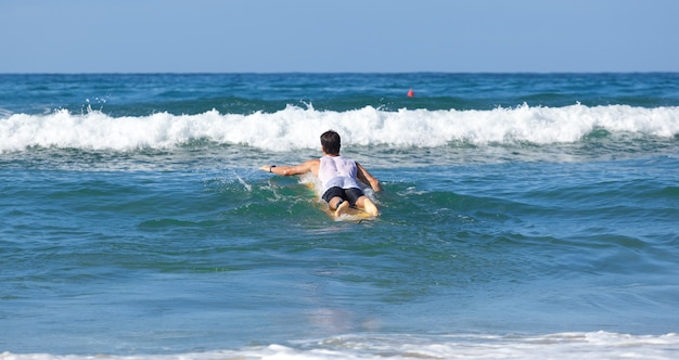 Surfer auf longboard reitet eine welle im meer