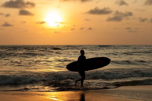 Surfer aus dem meer bei sonnenuntergang