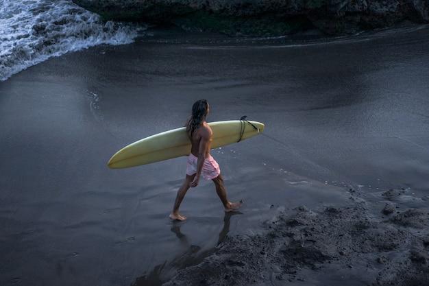 Surfer bei sonnenuntergang gehen mit einem surfbrett am meer entlang.