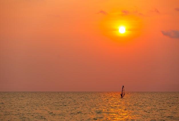 Surfer, der alleine in meer bei sonnenuntergang surft