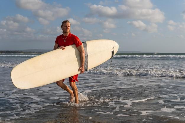 Surfer, der am strand entlang geht. bali
