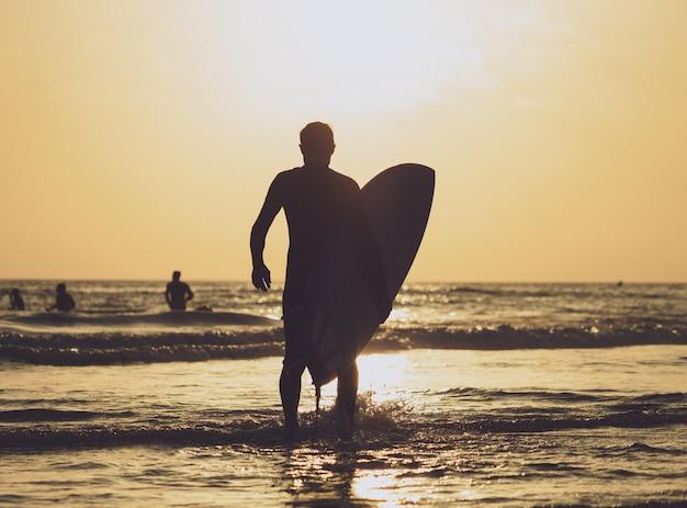 Surfer, der das brett zum meer zur sonnenuntergangzeit durchführt