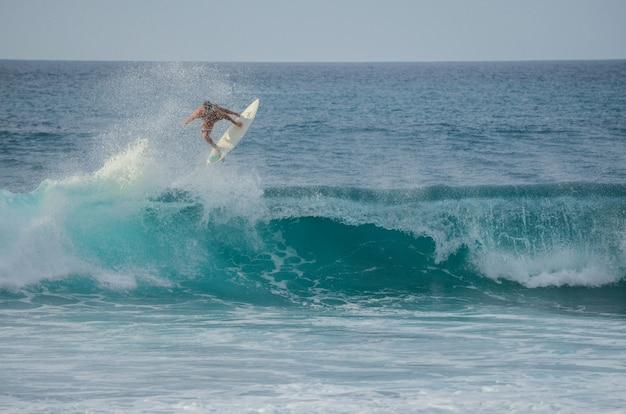 Surfer, der eine welle am felsigen punkt auf dem nordufer von oahu, hawaii, usa springt