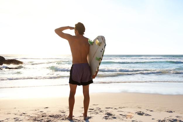 Surfer, der wellen im meer betrachtet