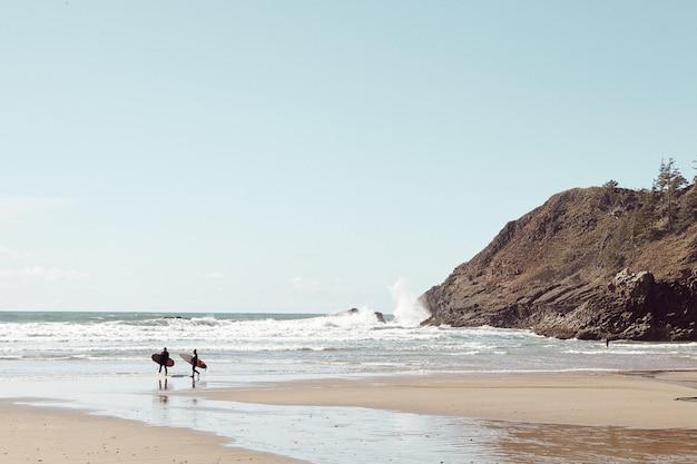 Surfer in der ferne am felsigen strand