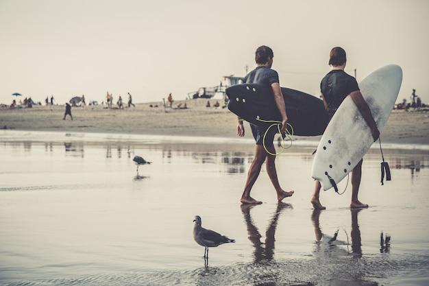 Surfer kehren vom meer zurück, nachdem sie aktiv in den wellen gesurft haben
