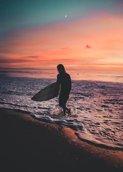 Surfer mit einem board, der bei sonnenuntergang aus dem meer geht