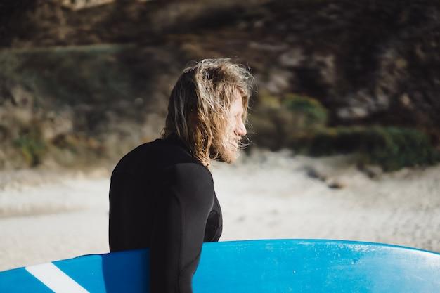 Surfer mit flossen und einem bodyboard in einem hydroanzug am ufer des ozeans