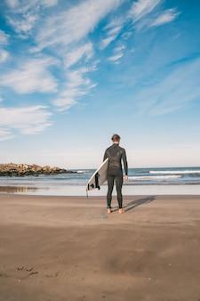 Surfer mit seinem surfbrett ins wasser.