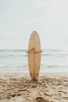 Surfer umarmt ein surfbrettmodell