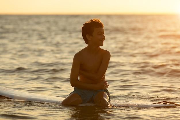 Surferjunge, der auf einem surfbrett an der dämmerung sitzt