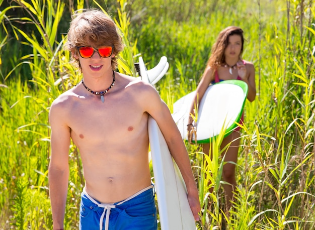 Surferjunge und -mädchen, die in den grünen dschungel gehen