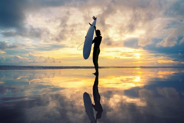 Surfermädchen, das am ozeanstrandsonnenuntergang surft