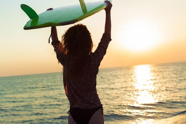 Surfermädchen, das ozeanstrandsonnenuntergang betrachtend surft