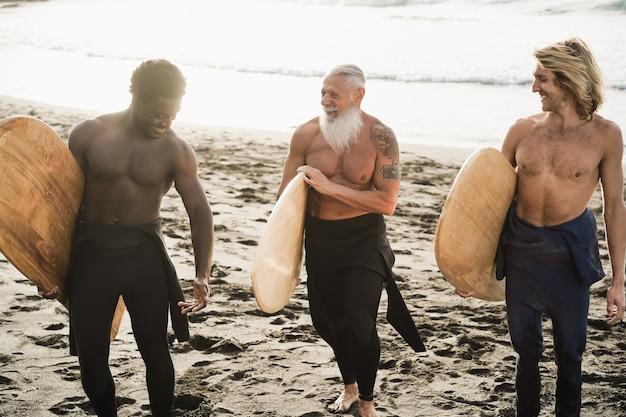 Surfermänner mit mehreren generationen, die spaß am strand haben - hauptaugenmerk auf seniorengesicht