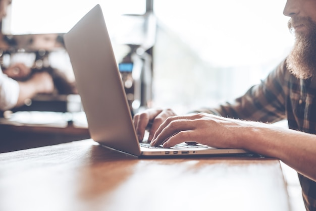 Surfnetz im café. nahaufnahme eines jungen bärtigen mannes, der seinen laptop benutzt, während er an der bartheke im café mit barista im hintergrund sitzt