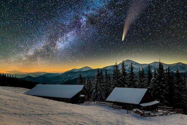 Surreale ansicht der nacht in den bergen mit sternenklarem dunkelblauem bewölktem himmel und kometen c / 2020 f3 (neowise) mit hellem schwanz.