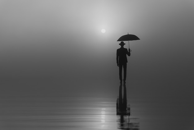 Surreale silhouette eines mannes in anzug und hut mit einem regenschirm, der bei sonnenaufgang an einem nebligen morgen auf dem wasser steht