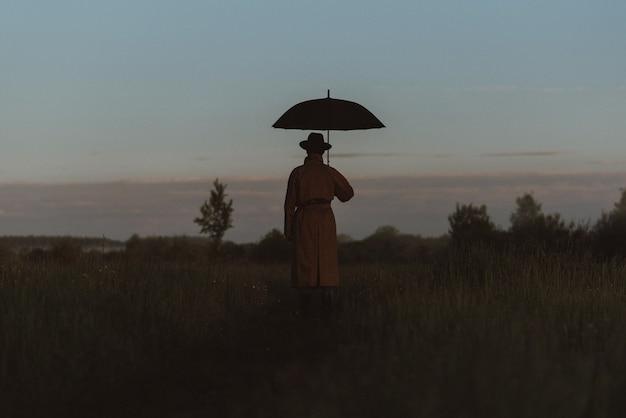 Surreale silhouette eines mannes in einem anzug mit regenschirm, der in einem regenmantel auf einem feld steht
