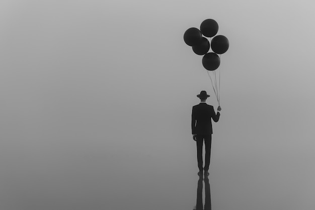 Surrealer einzelner mann in einem anzug mit einem hut mit luftballons in der hand auf dem wasser am morgen im nebel