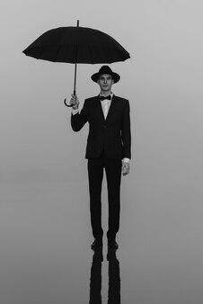 Surreales porträt eines mannes in anzug und hut mit einem regenschirm, der auf dem wasser steht