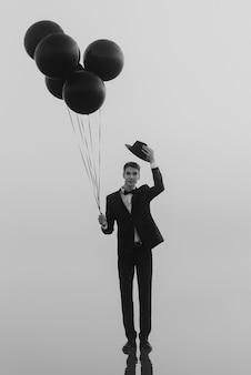 Surreales porträt eines mannes mit luftballons in der hand auf dem wasser im nebel