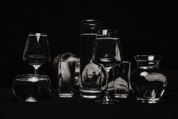 Surreales schwarzweiss-porträt eines mannes, der durch gläser des wassers auf einem schwarzen hintergrund schaut