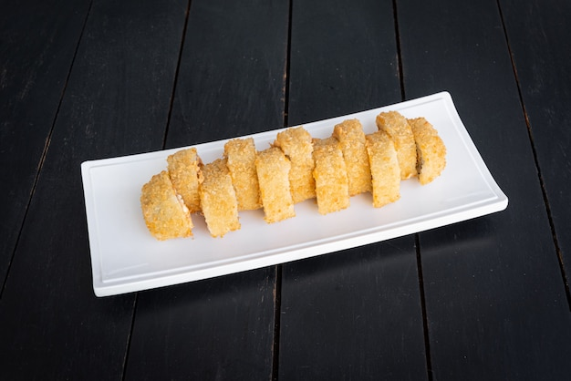 Sushi auf dem teller auf dem schwarzen tisch