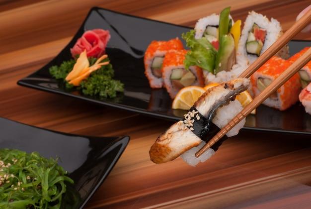 Sushi auf stäbchen hautnah auf einem hintergrund von sushi-gerichten