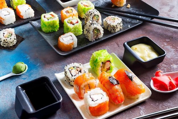 Sushi, brötchen, essstäbchen, sojasauce auf duotoner schieferoberfläche