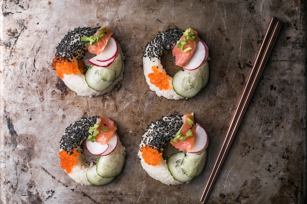 Sushi donuts mit lachs, gurke und radieschen auf metall draufsicht