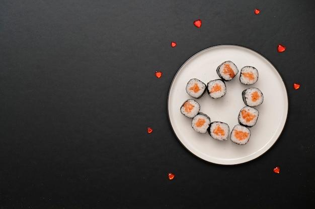 Sushi für valentinstag - rollen sie in der herzform, auf platte auf schwarzem hintergrund. platz für text.