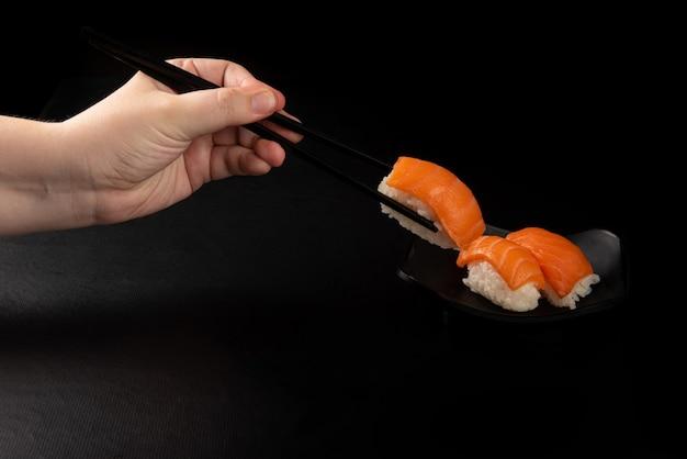 Sushi, hände, die sushi mit haschi pflücken