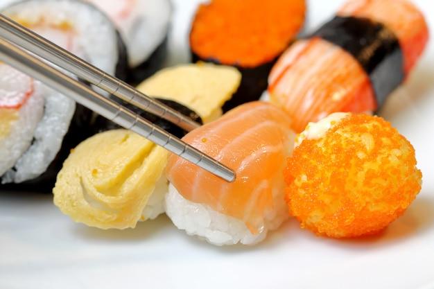 Sushi halten stäbchen und in die sauce getaucht.