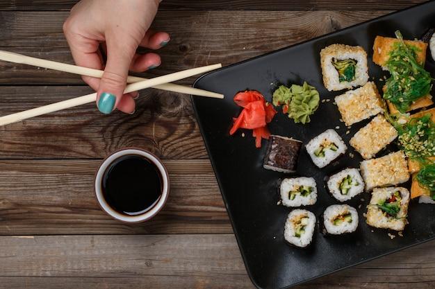 Sushi. hand mit essstäbchen