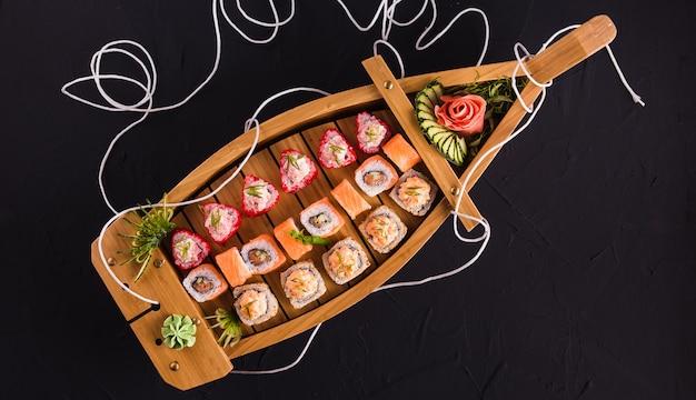 Sushi in einem holzboot auf einer schwarzen oberfläche (draufsicht)