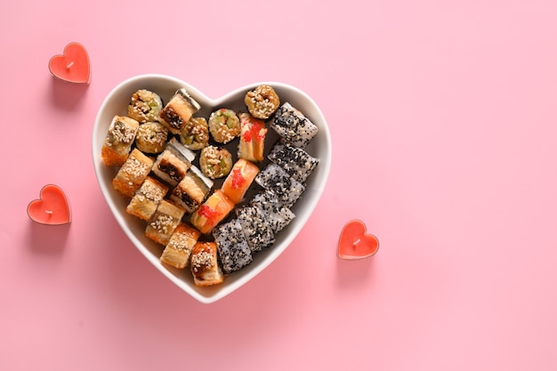 Sushi in platte als herz auf rosa hintergrund gesetzt. valentinstag food-konzept. von oben betrachten. platz für text. flatlay-stil.