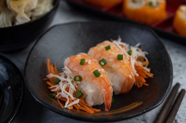 Sushi ist in einem teller mit stäbchen und dip auf einem weißen zementboden.