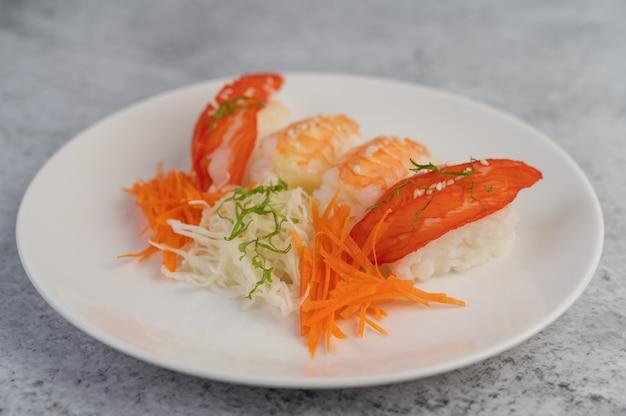 Sushi ist wunderschön auf dem teller angeordnet.