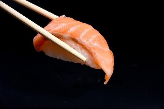 Sushi lachs nigiri in stäbchen über schwarz