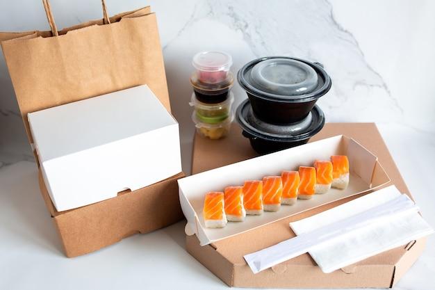 Sushi-lieferung lieferung von köstlichem, schönem sushi in einem paket lebensmittellieferung nach hause in handwerk