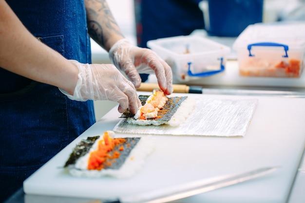 Sushi lieferung. maskierte und behandschuhte köche bereiten sushi in der küche des restaurants zu.