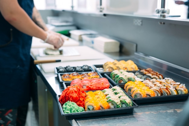 Sushi lieferung. viele sorten von sushi in einer plastikbox werden für die lieferung vorbereitet.