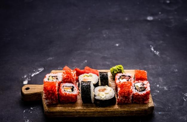 Sushi maki set japanische asiatische rolllebensmittelzusammensetzung mit zubereitetem reis und meeresfrüchten nach traditionen